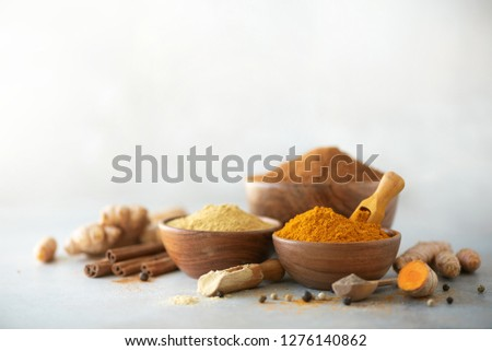Ingredients for turmeric latte. Ground turmeric, curcuma root, cinnamon, ginger, black pepper on grey background. Spices for ayurvedic treatment. Alternative medicine concept. #1276140862