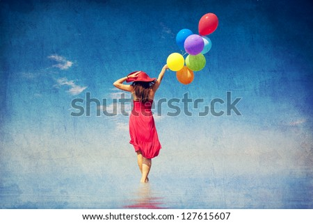 Brunette girl with colour balloons at coast. Photo in old color image style.