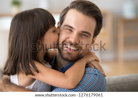 Portrait of cute kid daughter embracing kissing on cheek young happy single dad looking at camera, little child girl congratulating smiling daddy celebrating fathers day hugging cuddling showing love #1276179061
