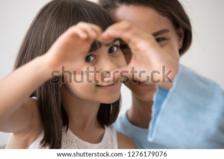 Portrait of little happy girl and mother join hands forming heart shape as concept of giving love, child mum connection unity, cute kid daughter and mom bonding looking at camera, child care adoption #1276179076