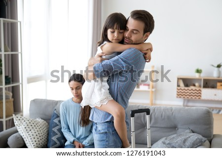 Sad little girl upset by father leaving embracing dad, depressed child saying goodbye hugging daddy going away, kid and parents divorcing breaking up, family separation, shared custody concept #1276191043