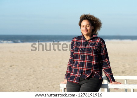 Portrait of young african american woman relaxing with eyes closed at the beach #1276191916