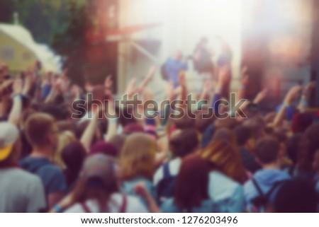 Vibrant pop music concert background.Big group of happy young people partying on musical festival in night club.Colorful abstract back ground for nightclub party poster.Fans hands and bright lights #1276203496
