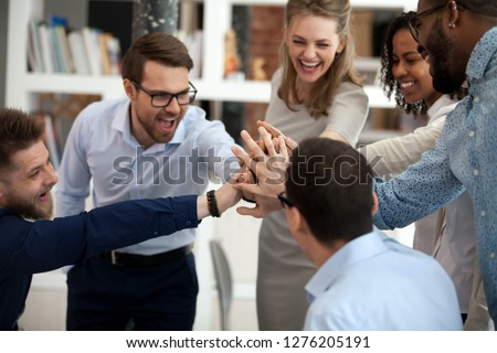 Excited motivated multi-ethnic team people give high five, happy diverse office employees executive group celebrate corporate success, sharing victory, engaged in unity support teambuilding concept #1276205191
