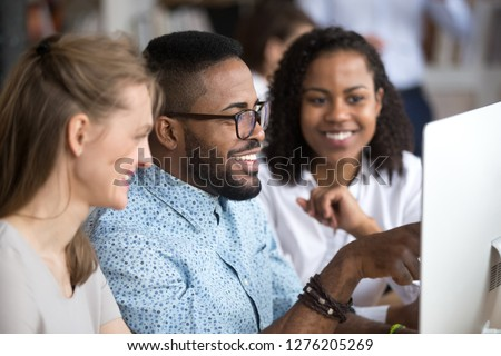 Smiling african employee team leader explaining computer task online project in office, happy black worker mentor talking teaching helping coworkers group, diverse colleagues work together on pc Royalty-Free Stock Photo #1276205269