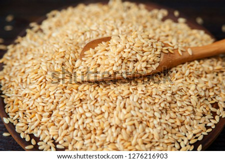 Pile of flax seeds with a wooden spoon on the table. #1276216903