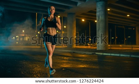 Beautiful Fitness Girl in Black Athletic Top and Shorts is Jogging on the Street. She is Doing a Workout in an Evening Wet Urban Environment Under a Bridge. #1276224424