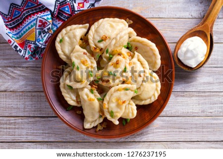 Dumplings, filled with cabbage. Varenyky, vareniki, pierogi, pyrohy - dumplings with filling. View from above, top studio shot #1276237195