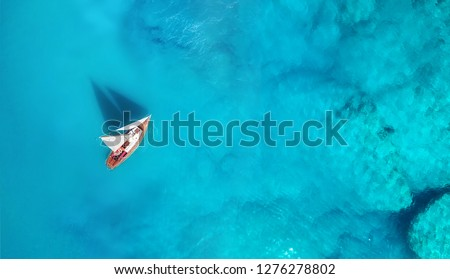 Yacht on the water surface from top view. Turquoise water background from top view. Summer seascape from air. Travel concept and idea #1276278802