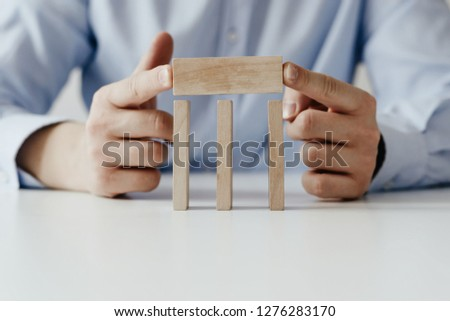 Businessman in a blue shirt arranges wooden jigsaw blocks. The man arranges empty blocks one on top of the other. Different concepts to supplement with content. Business concept, HR. #1276283170