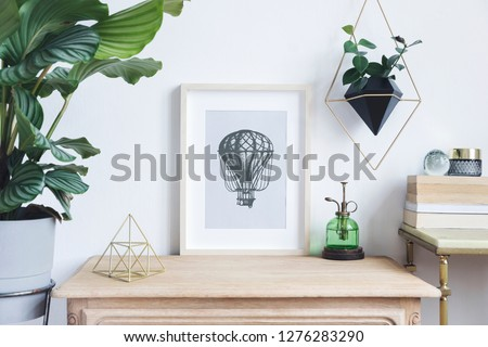 The room interior with mock up photo frame on the retro wooden shelf. Hanging plant in design pot, tropical plant, gold pyramid, design coffe table with books. Concept of minimalistic retro shelf.  #1276283290