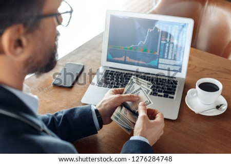 Mature man trader sitting at table at cafe with cup of coffee looking at laptop with trading chart counting dollar banknotes back view close-up #1276284748