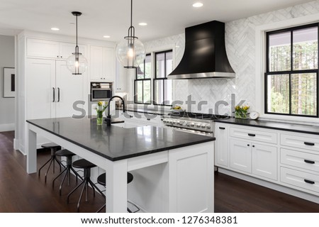 Beautiful Kitchen in New Luxury Home with White Cabinets and Black Accents, including Black Island Countertop. Features Hardwood Floors, Eating Nook, Island with Sink, and Built-In Refrigerator. #1276348381