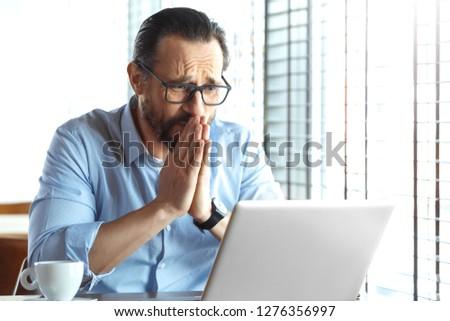 Mature man trader wearing eyeglasses sitting at table at cafe at daytime with laptop looking at screen praying hard for good investment #1276356997
