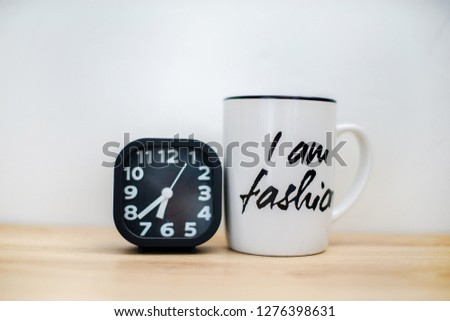 Modern black alarm clock next to coffee mug, wooden desk front concrete wall background. With copy space.  #1276398631