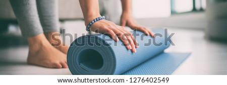 Yoga at home active lifestyle woman rolling exercise mat in living room for morning meditation yoga banner background. Royalty-Free Stock Photo #1276402549