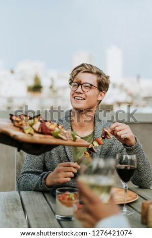 Happy man being served with vegan barbeque skewers #1276421074