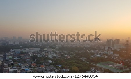 Buildings in city in early morning with golden sun light and fog at far away #1276440934
