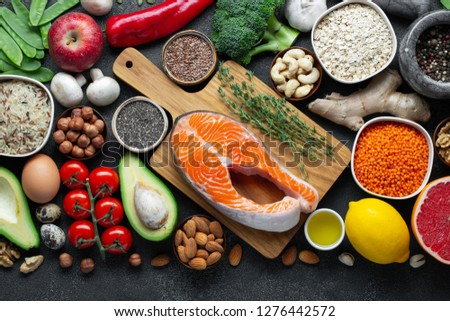 Healthy food clean eating selection: fish, fruit, nuts, vegetable, seeds, superfood, cereals, leaf vegetable on black concrete background. Flat lay #1276442572