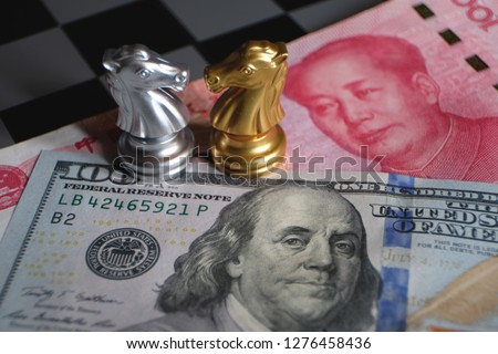 Chess game, two knights face to face on Chinese yuan and US dollar background. Trade way concept. Conflict between two big countries, USA and China concept. Copy space for text. #1276458436