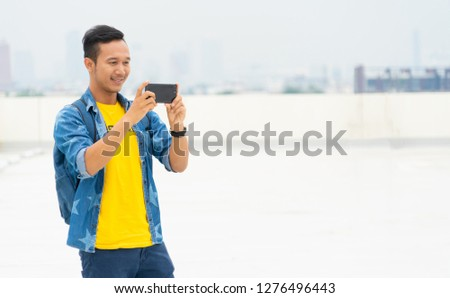 attractive and Charming man using digital smartphone technology to take photography in the city outdoor. asian handsome man in yellow casual shirt. Happy travel guy smiling outdoor #1276496443