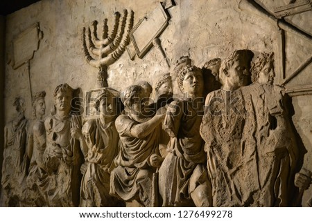 Wall relief on arch of titus depicting Menorah taken from temple in Jerusalem in 70 AD - Israel history, Jewish war Royalty-Free Stock Photo #1276499278