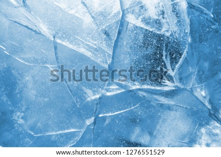 Abstract ice background. Blue background with cracks on the ice surface #1276551529