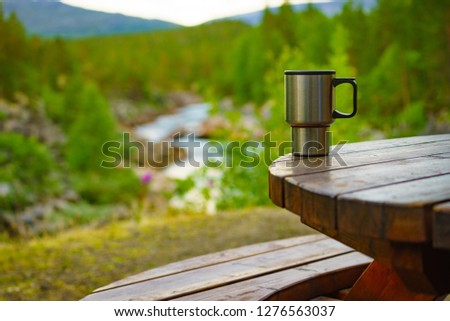 Picnic site table with thermal mug, norwegian mountains nature in the background. Camping with thermos. #1276563037