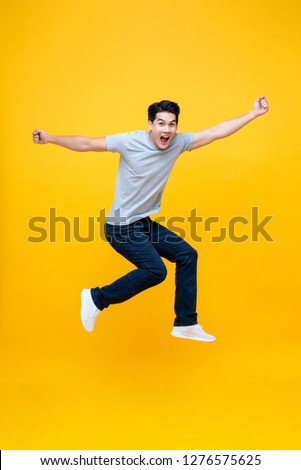 Energetic excited young Asian man in casual clothes jumping studio shot isolated in colorful yellow background #1276575625