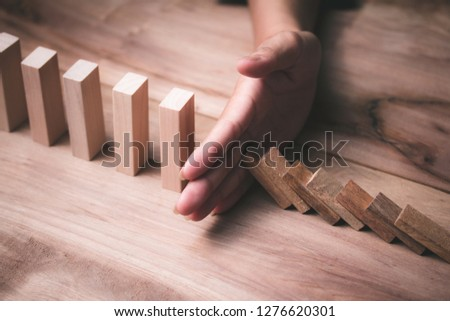 Wooden game strategy, Businessman hand stopping risk falling wooden dominoes effect Create stability for the company #1276620301