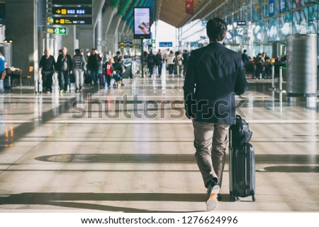 Close up of businessman carrying suitcase while walking through a passenger departure terminal in airport. Businessman traveler journey business travel. #1276624996