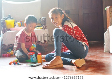 Native american kids playing with plastic blocks in old house.  #1276637173
