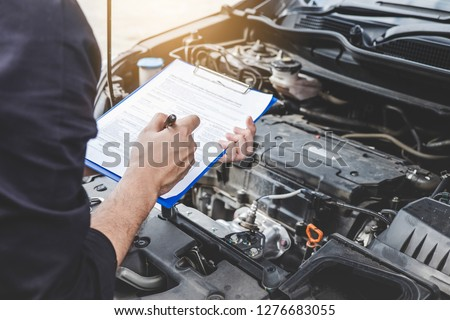 Services car engine machine concept, Automobile mechanic repairman checking a car engine with inspecting writing to the clipboard the checklist for repair machine, car service and maintenance. #1276683055