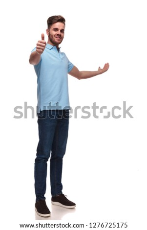 casual man presents to side while making thumbs up sign and standing on white background, full length picture