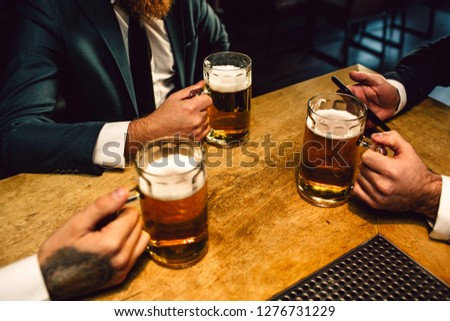 Picture of mn in suits sit at table. They hold mugs of beer and one phone.