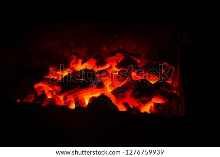 Hot wooden coals in the dark. Grill with hot coals and beautiful magic sparks with blue flame #1276759939