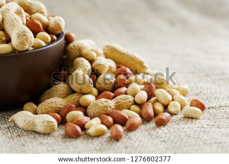 Peanuts in the shell and peeled closeup in a cup #1276802377
