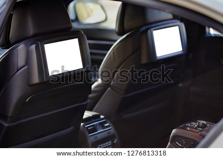 Car inside headrest screen mock up. Interior of prestige luxury modern car. Two white displays for back seats passenger with media control panel copy space and place for text. Royalty-Free Stock Photo #1276813318