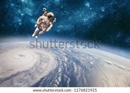 Astronaut in outer space against the backdrop of the planet earth. Typhoon over planet Earth. Elements of this image furnished by NASA. #1276821925