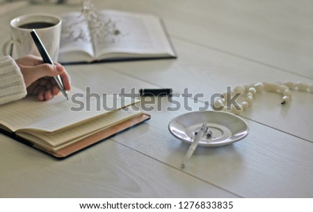 Morning mood female hands a cup of coffee, a notebook and a smoking cigarette on a white wooden table #1276833835