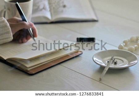 Morning mood female hands a cup of coffee, a notebook and a smoking cigarette on a white wooden table #1276833841