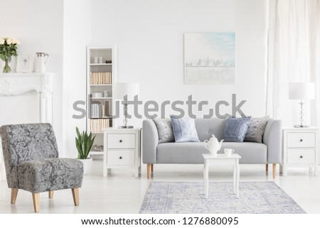Armchair near white table on carpet in apartment interior with poster above grey settee. Real photo #1276880095