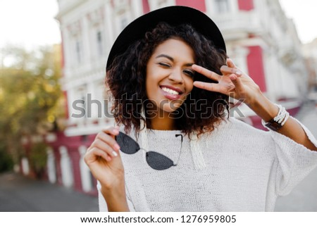 Cute black woman posing outdoor. Showing signs and smiling. Happy emotions. fashion look. Traveling girl.  #1276959805