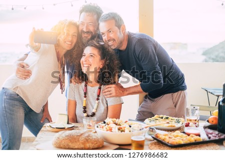 Group of friends have fun together during a lunch outdoor in the terrace at home and taking a modern selfie with smart phone to share on social media accounts for internet life - web addicted happy #1276986682