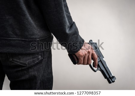 A man holding a gun in hand, the ship ready to shoot the man pointed a gun at us. A man holding a gun was robbed. #1277098357