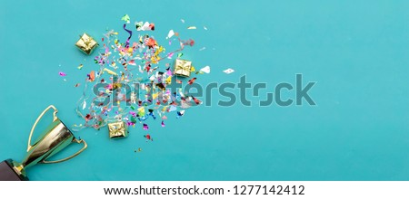 Panorama concept. Celebrating the success that has happened, Gold trophy placed on a blue background. There are gift boxes and colorful ribbons. Free space to put text into advertising media. Royalty-Free Stock Photo #1277142412