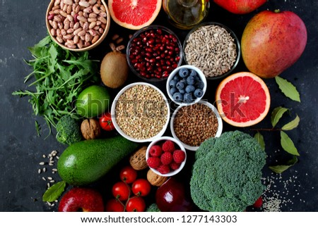Healthy food concept. Vegetarian and vegan food: vegetables, fruits, seeds, legumes, leaf vegetables on dark background. Diet food. Top view. #1277143303