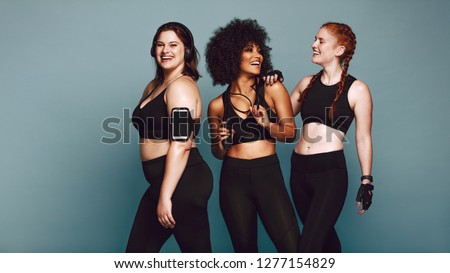 Multi-ethnic group of women together against grey background and smiling. Diverse group females in sportswear after workout. #1277154829