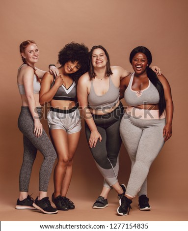 Group of women of different race, figure type and size in sportswear standing together over brown background. Diverse women in sports clothing looking at camera and laughing. #1277154835