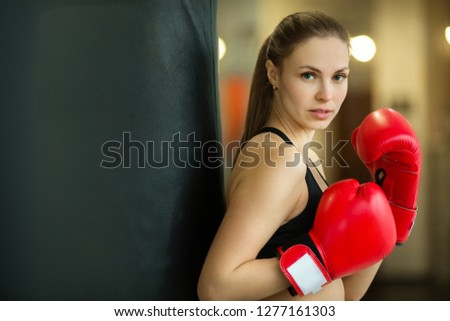 beautiful young girl engaged in training in the gym with boxing gloves #1277161303